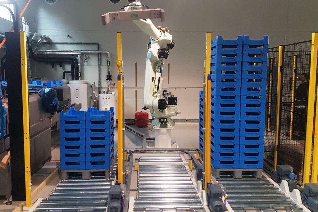 Kawasaki CX210L robot hanteert kratten met meelwormen in een kwekerij in Scandinavië. Palletiseren en depalletiseren van kratten.